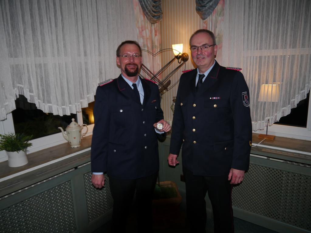 """Jörg Suske (rechts) ehrt Meik Mahnstein (links) mit einem """"Coin"""" für die geleistete Arbeit beim Flächenbrand in Meppen."""
