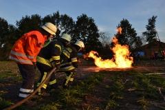 Geduckte Feuerwehrleute vor Feuer